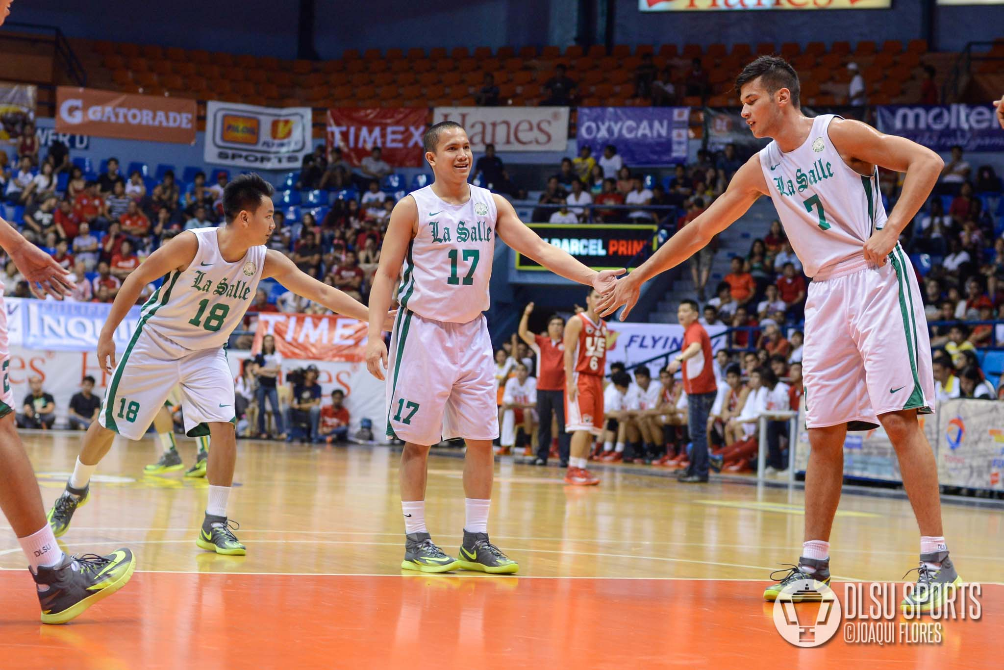 Thomas Torres (left) and Arnold van Opstal (right) tapos Almond Vosotros (middle) after making a free throw.